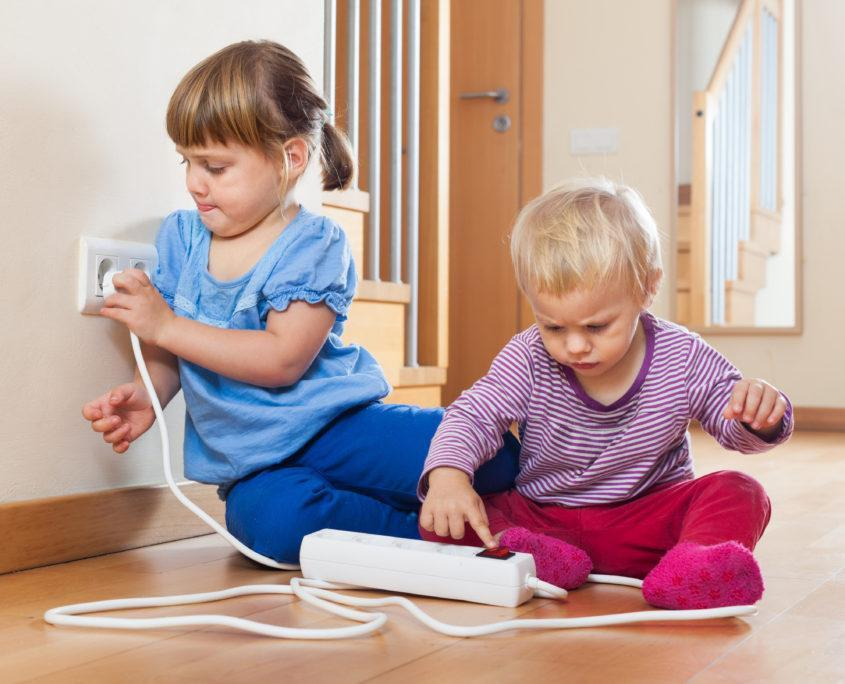 Two children playing with electrical extension and outlet on floor at home